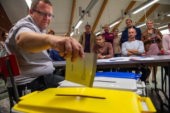 Valförrättare under valkvällens rösträkning lägger i valkuvert i urnan, ryska deltagare tittar på. Fotograf Erland Segerstedt