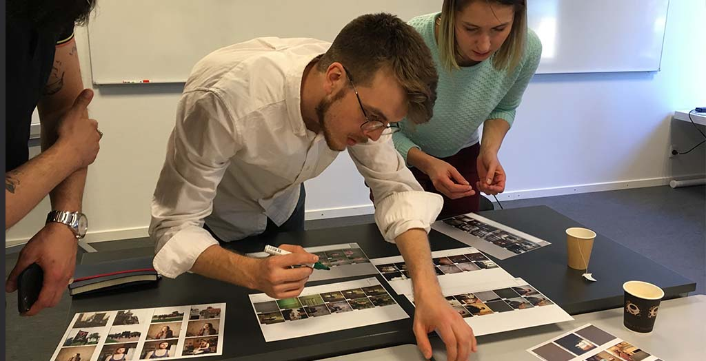 Deltagere på Next to Me i 2018 udvælger fotografier til fælles udstilling og fotobog. Foto: Mads Greve